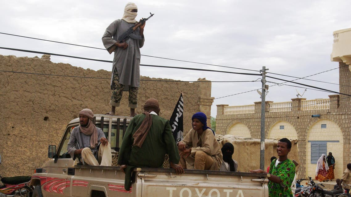 In this Aug. 31, 2012 file photo, fighters from the al-Qaida-linked Islamist group Ansar Dine stand guard in Timbuktu, Mali, as they prepare to publicly lash a member of the Islamic Police found guilty of adultery. (AP)