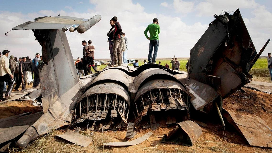 Libyans inspect the wreckage of a US F15 fighter jet after it crashed in an open field in the village of Bu Mariem, east of Benghazi, eastern Libya, Tuesday, March 22, 2011, with both crew ejecting safely. AP