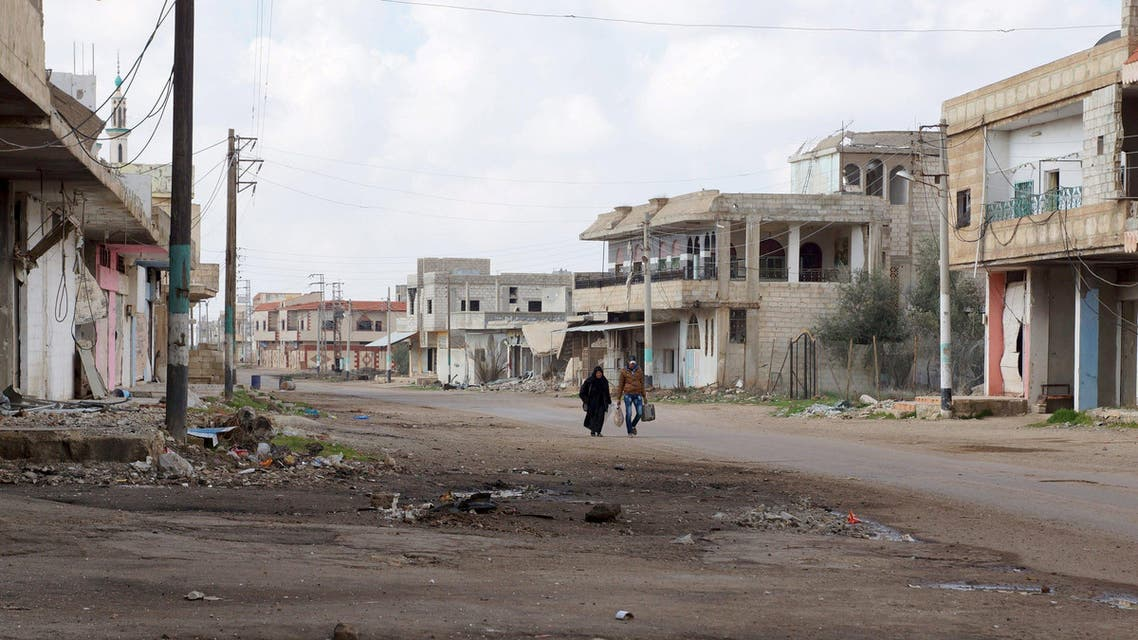 Civilians walk along a deserted street in the rebel held al-Ghariyah al-Gharbiyah town, in Deraa province, Syria February 11, 2016. REUTERS