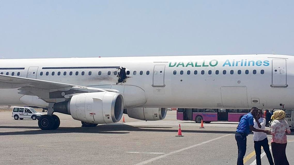 In this photo taken Tuesday, Feb. 2, 2016, a hole is seen in a plane operated by Daallo Airlines as it sits on the runway of the airport in Mogadishu, Somalia. A gaping hole in the commercial airliner forced it to make an emergency landing at Mogadishu's international airport late Tuesday officials and witnesses said. (AP Photo)