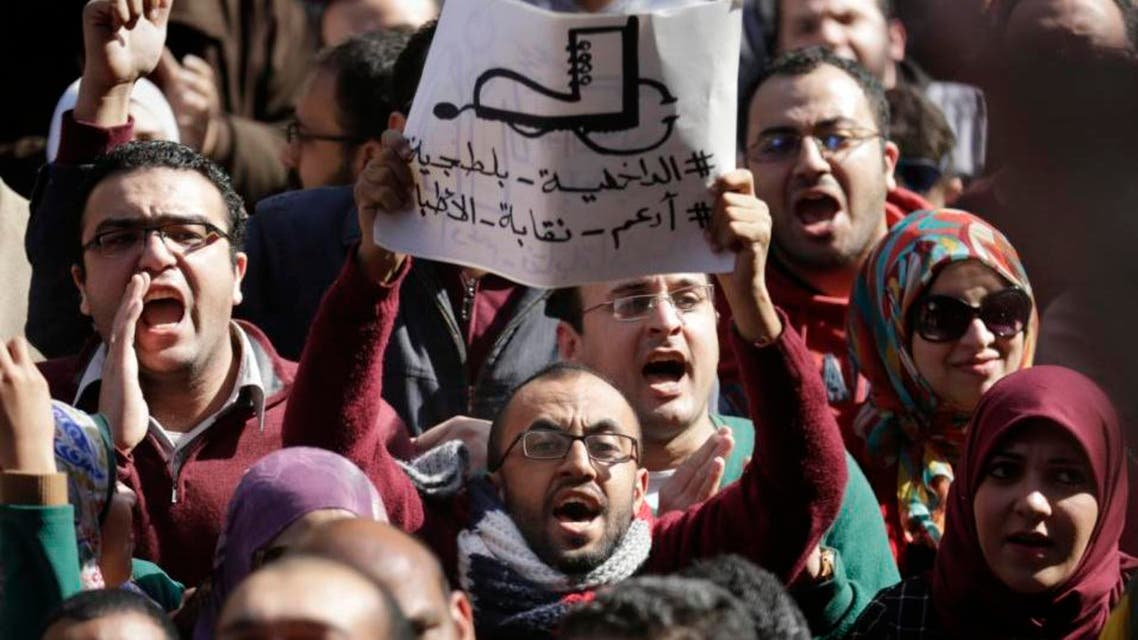 """Egyptian doctors shout anti-police slogans as one holds a banner showing a police boot stepping on a medical stethoscope with Arabic slogan reading, """"police are thugs."""" (AP)"""