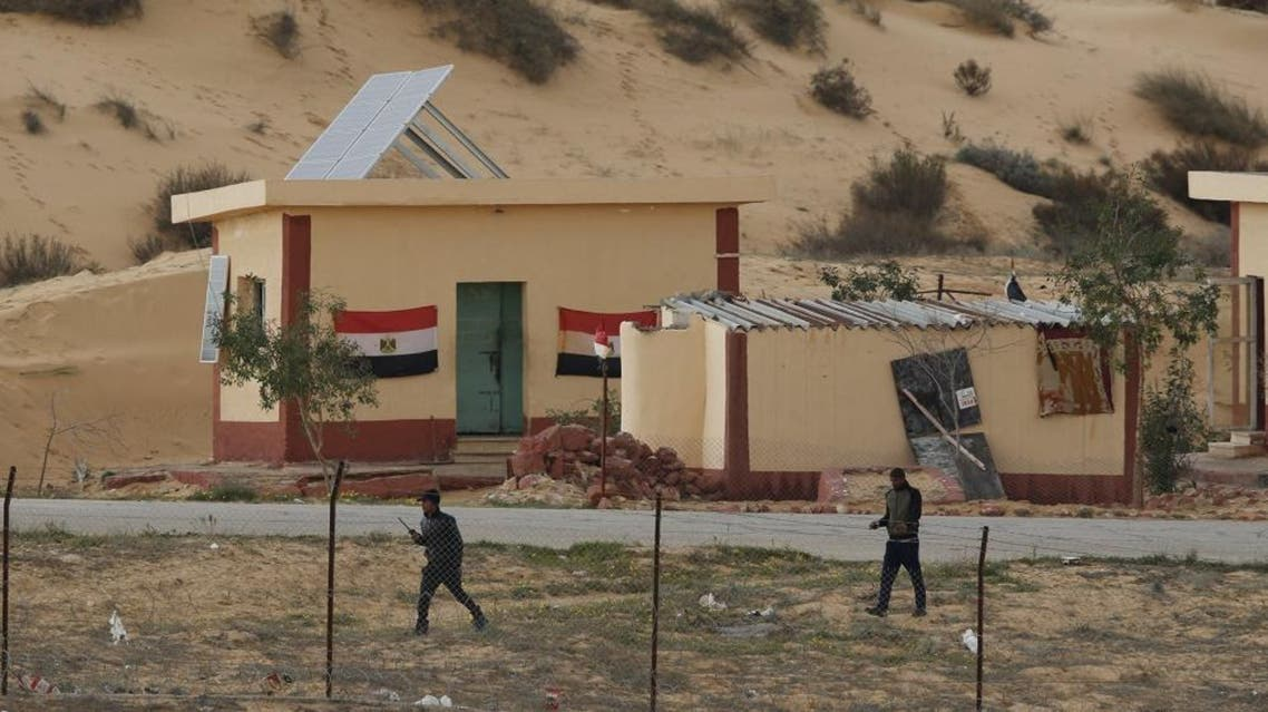Egyptian policemen walk next to a border post, as seen from the Israeli side of the border with Egypt's Sinai peninsula, in Israel's Negev Desert February 10, 2016. REUTERS/Amir Cohen