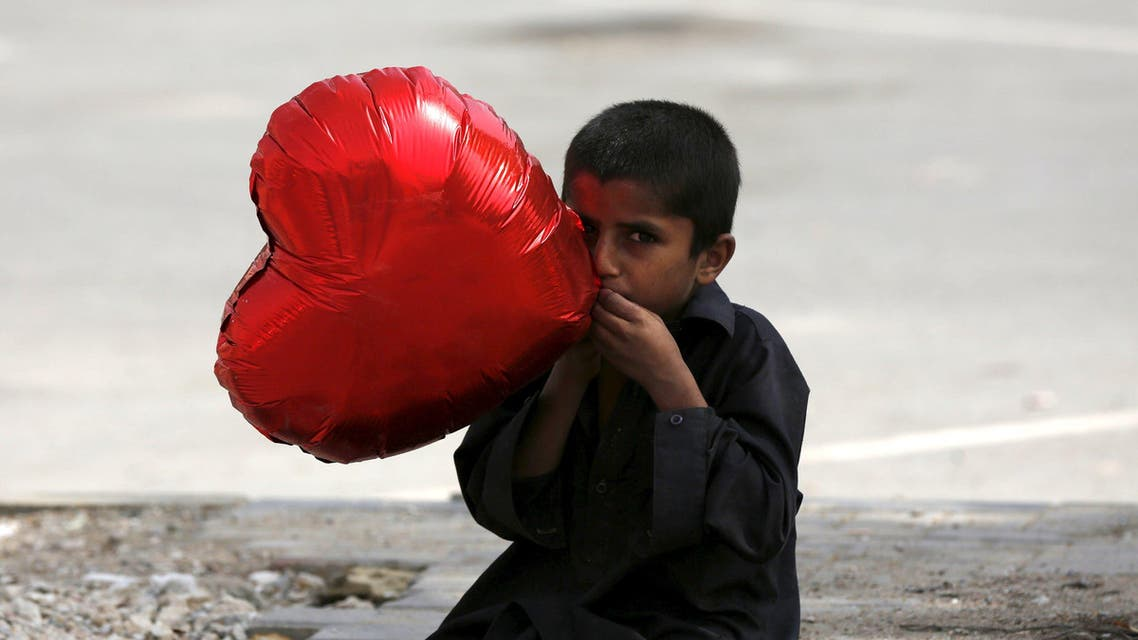 A boy inflates a heart-shaped balloon to sell on Valentine's Day in Karachi, Pakistan February 14, 2016. (Reuters)