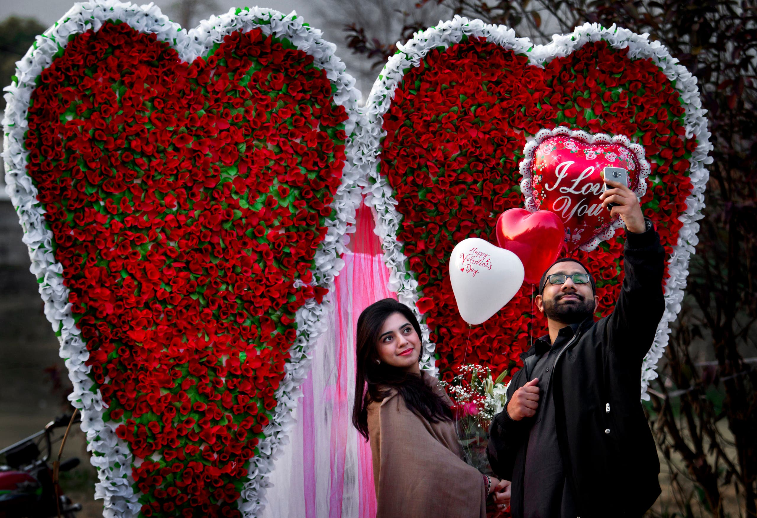 A couple take 'selfie' in front of a giant heart-shaped bouquet display by a vendor to attract customers on Valentine's Day, Sunday, Feb. 14, 2016. (AP)