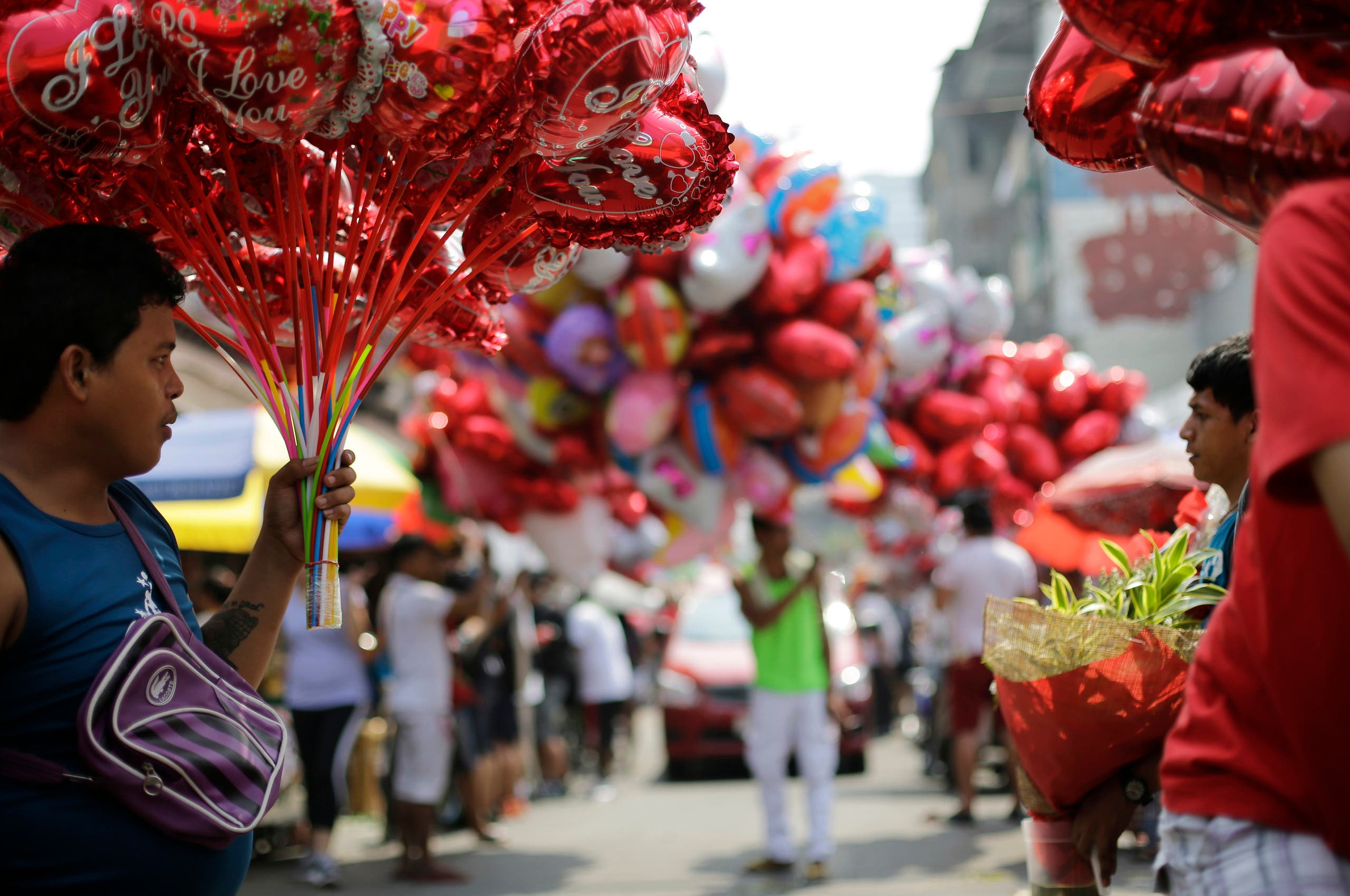 A Filipino sells hear-shaped balloons at a flower market in Manila, Philippines on Valentine's Day, Sunday, Feb. 14, 2016. (AP)