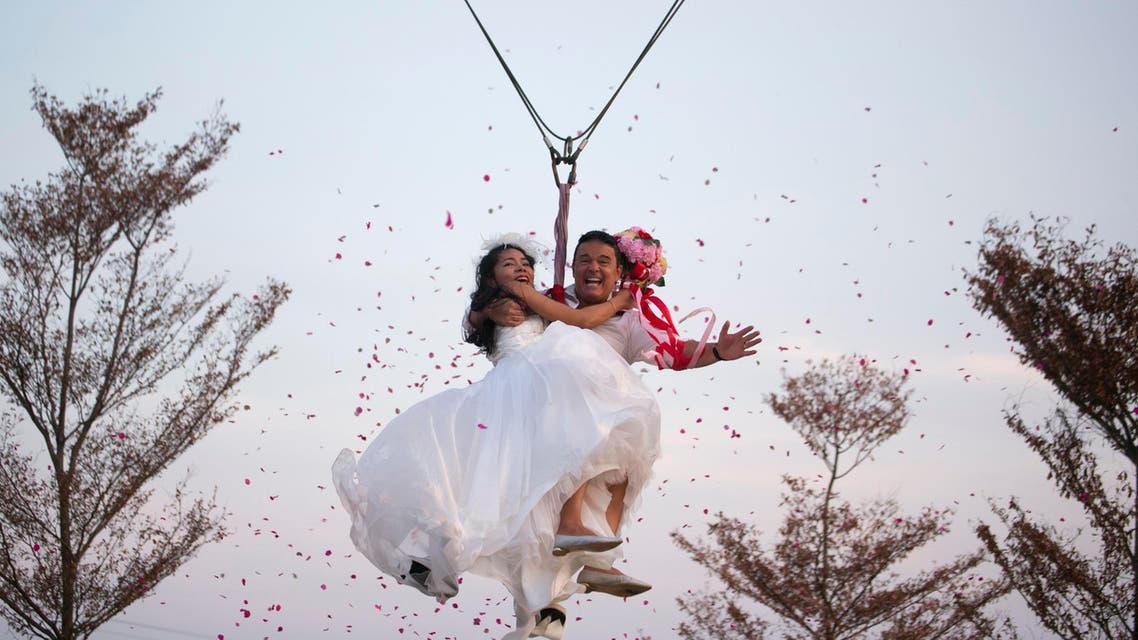 Bride Charunee Koydun and groom British David Leslie Chesterman celebrate Valentine's Day as they take to the skies in a 'sky coaster' as part of an adventure-themed wedding ceremony in Ratchaburi province Thailand, Saturday, Feb. 13, 2016, on the eve of Valentine's Day. (AP)