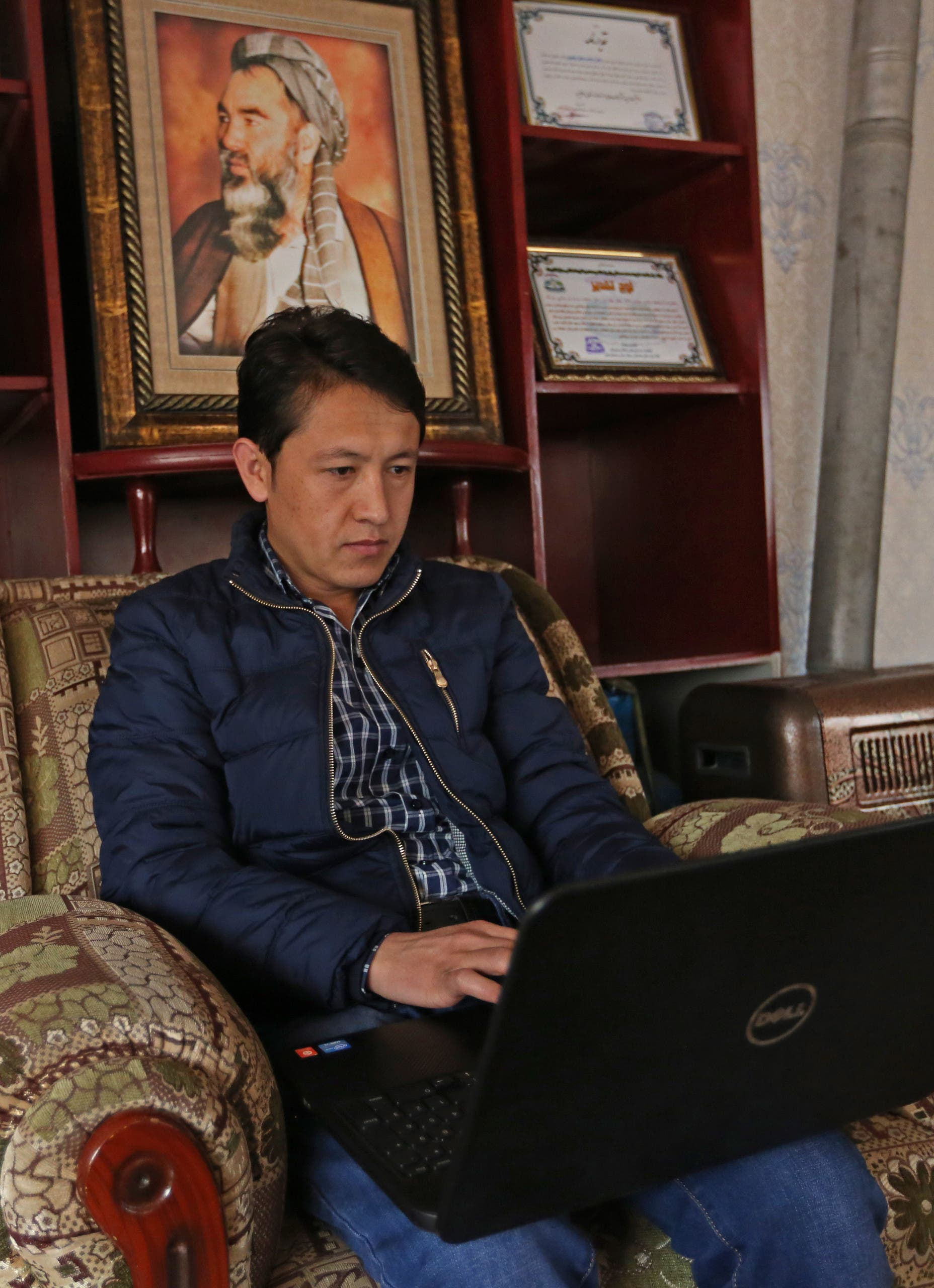 In this Monday, Feb. 8, 2016 photo, Afghan civil activist Hadi Sadiqi chats on Facebook with his wife Maleka Yawari from his office in Kabul, Afghanistan.