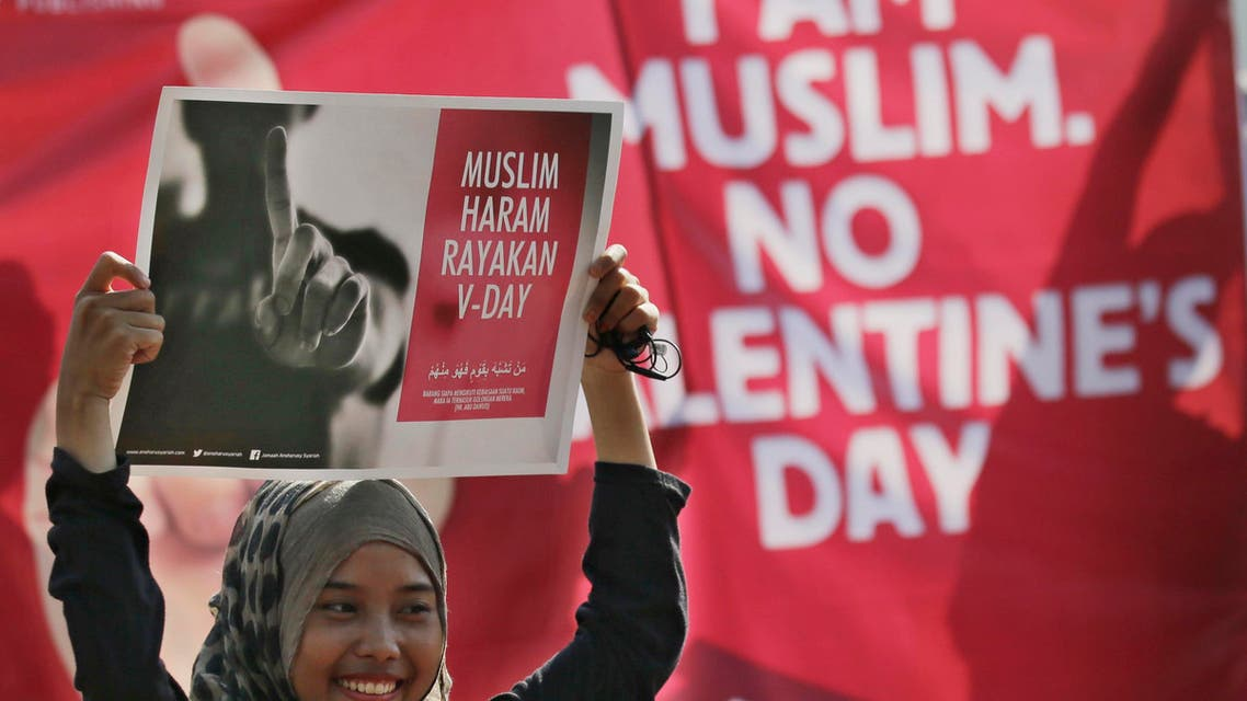 A Muslim girl displays posters 'Muslims forbidden to celebrate Valentine's Day' during a protest against Valentine's Day in Jakarta, Indonesia, Sunday, Feb. 14, 2016. (AP)