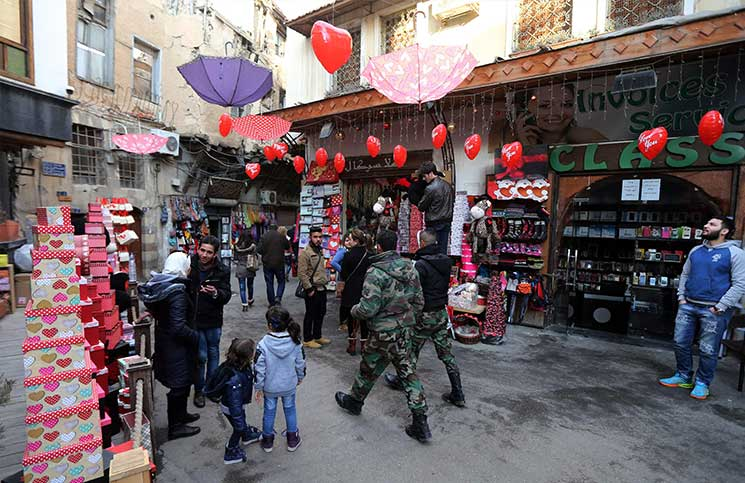 Syrian soldiers walk past shops displaying gifts for Valentine's Day in Damascus. (AFP)