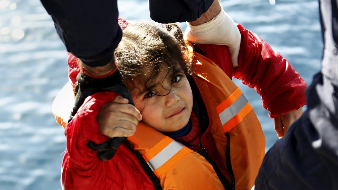 Greek Coast Guard officers move a girl from a dinghy carrying refugees and migrants aboard the Ayios Efstratios Coast Guard vessel, during a rescue operation at open sea between the Turkish coast and the Greek island of Lesbos, February 8, 2016. AP