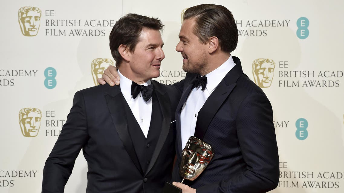 Leonardo DiCaprio holds his award for best leading actor as he embraces presenter Tom Cruise at the British Academy of Film and Television Arts (BAFTA) Awards at the Royal Opera House in London, February 14, 2016