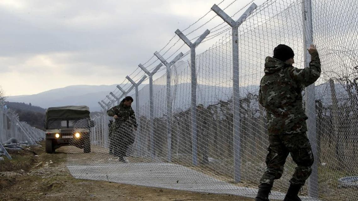 "In this February 8, 2016 file photo, Macedonian Army soldiers erect a second fence on the border line with Greece, near the southern Macedonia's town of Gevgelija. Six nations from Central and Eastern Europe meet Monday in Prague to discuss plans for a new ""line of defense"" for Europe that involves a double fence along Greece's northern border (AP)"