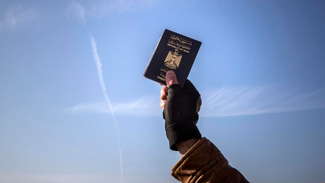 A refugee holds up his Iraqi passport at the port of Molyvos after a rescue operation by members of the Frontex, European Border Protection Agency, from Portugal near the northeastern Greek island of Lesbos. (File photo: AP)