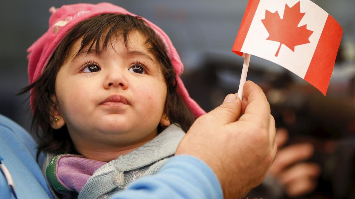 A Syrian refugee looks up as her father holds her and a Canadian flag as they arrive at Pearson Toronto International Airport in Mississauga, Ontario, December 18, 2015. (Reuters)