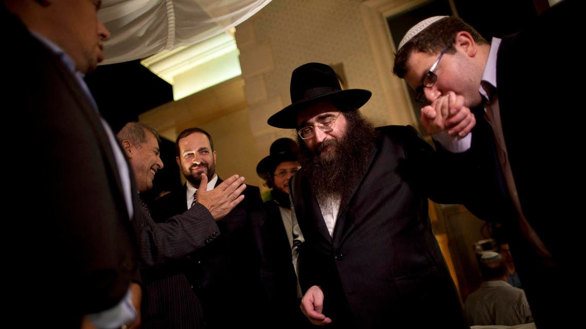 FILE - In this July 11, 2011 file photo, a man kisses the hand of Rabbi Yoshiyahu Pinto at a wedding in Lod, central Israel. An Israeli prison spokeswoman said Pinto, a celebrity rabbi with a following in the United States, has reported to prison on Tuesday, Feb. 16, 2016, to begin a one-year sentence for bribery. (AP Photo/Oded Balilty, File)