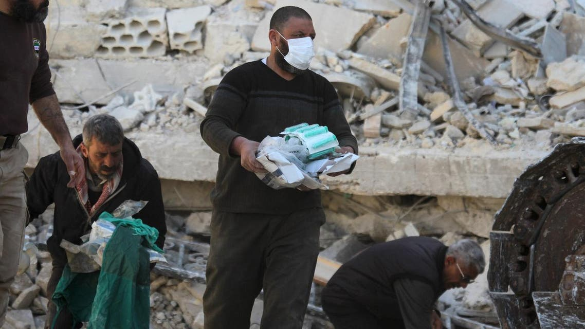 People carry medical supplies found under the rubble of a destroyed Medecins Sans Frontieres (MSF) supported hospital hit by missiles in Marat Numan, Idlib province, Syria. (Syria)