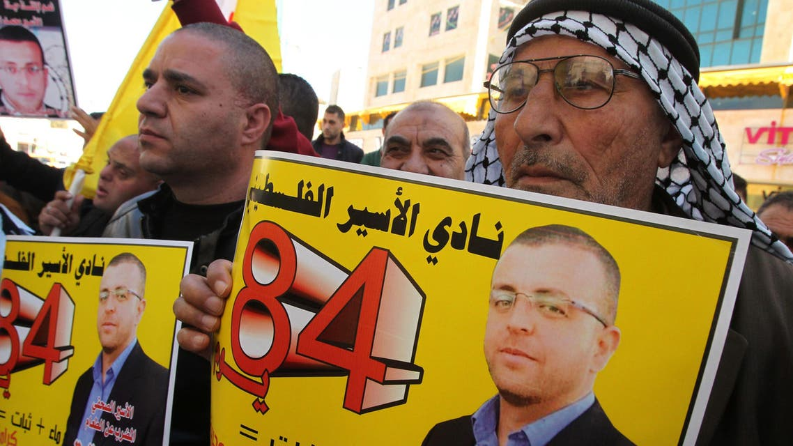 Palestinians take part in a demonstration calling for the release of Mohammed al-Qiq, a Palestinian prisoner on hunger strike, in the West bank town of Hebron. (AFP)