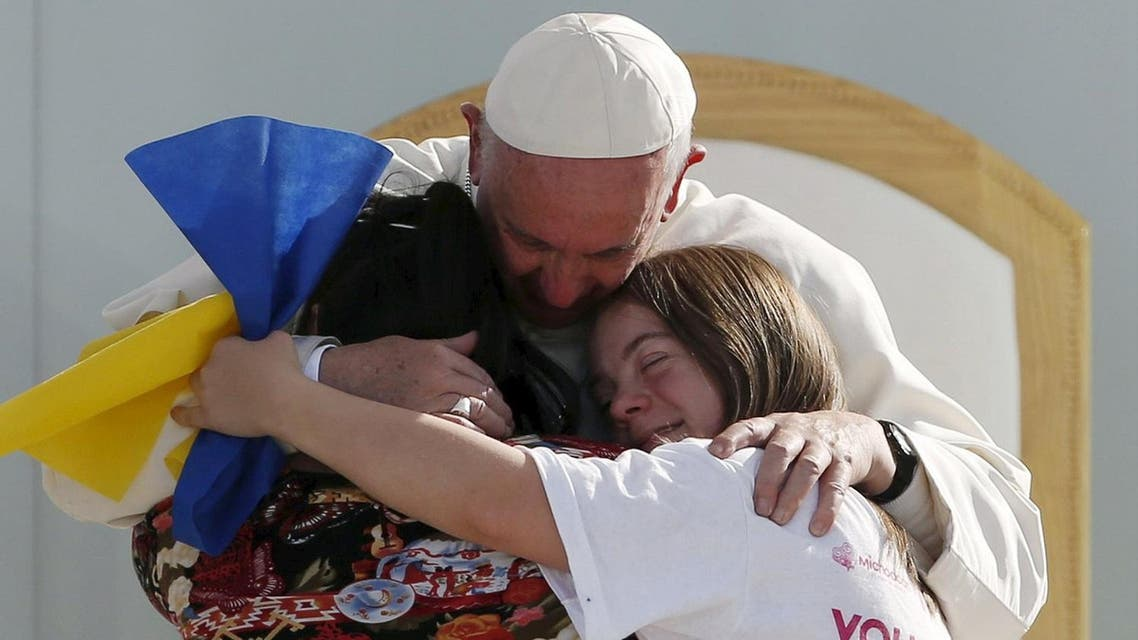 Pope Francis hugs two girls during a meeting with youths at the Jose Maria Morelos y Pavon stadium in Morelia. (Reuters)