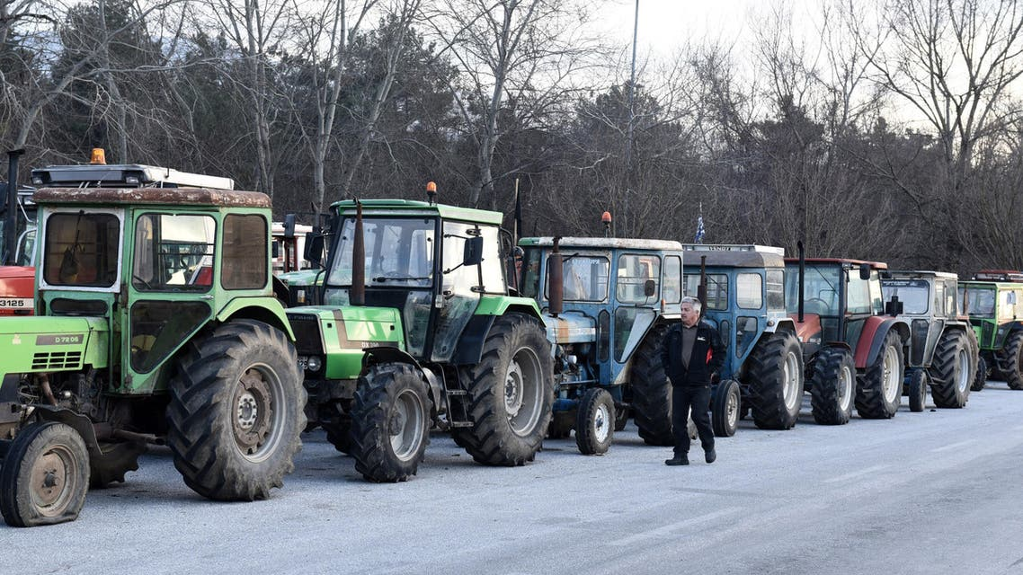 A protesting farmer walks next to parked tractors during a blockade in the northern Greek village of Promahonas village at the customs of the Greek-Bulgarian borderline on Monday, Jan. 25, 2016. Greek farmers angry at planned pension and tax reforms have expanded their campaign of blocking highways and closed a border crossing to Bulgaria, leaving dozens of trucks stranded on either side of the border. (AP Photo/Giannis Papanikos)