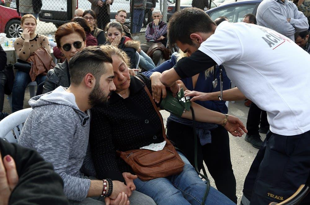 Medics give medical assistance to a relative of a victim outside the medical forensics in Ankara, Turkey, Thursday, Feb. 18, 2016. A Syrian national with links to Syrian Kurdish militia carried out the suicide bombing in Ankara that targeted military personnel and killed at least 28 people, Turkey's prime minister said Thursday. (AP Photo/Burhan Ozbilici)