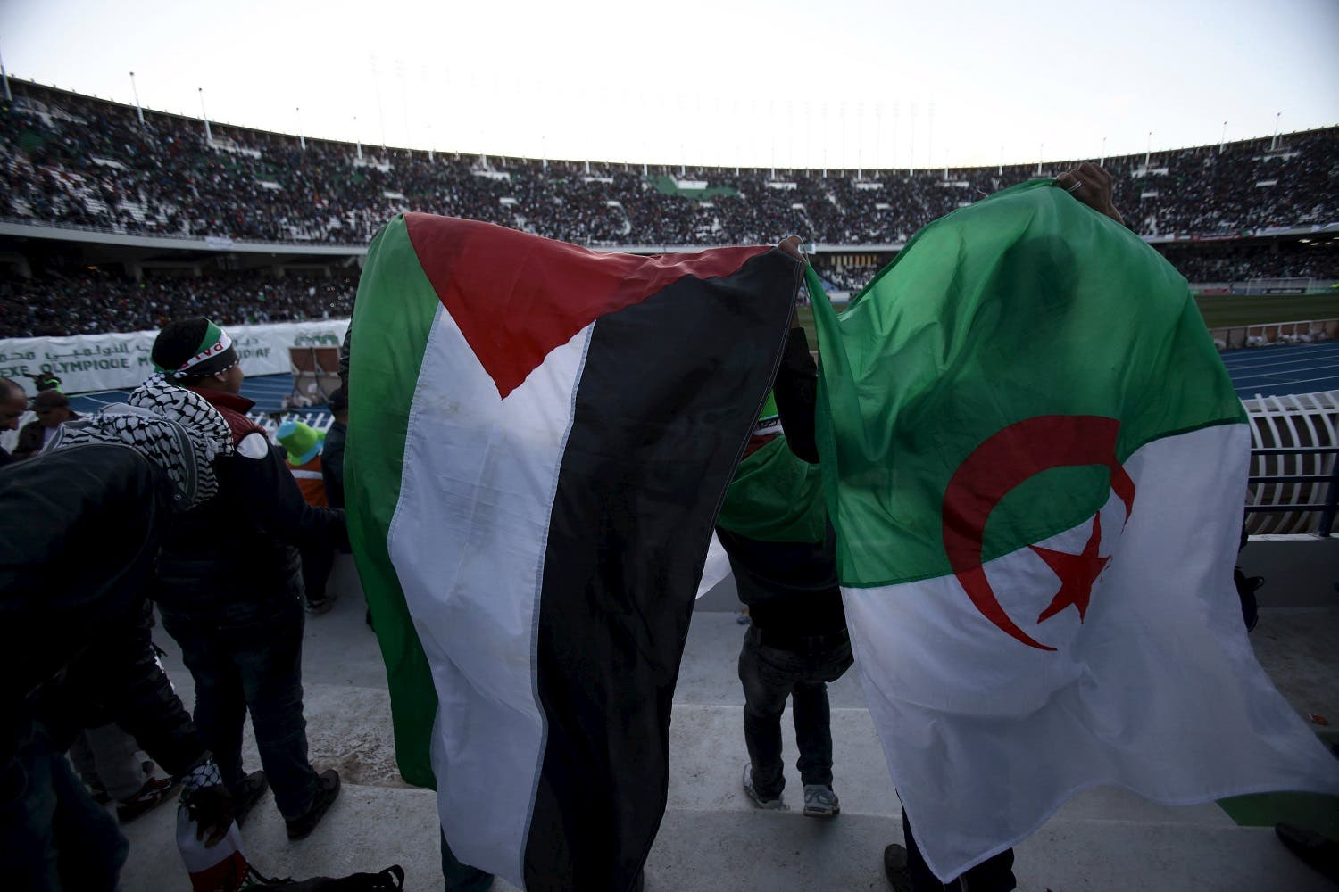 Algerian and Palestinian fans react during a friendly soccer match between the Palestinian and Algerian Olympic football teams at the du 5 Juillet 1962 stadium in Algiers. (Reuters)
