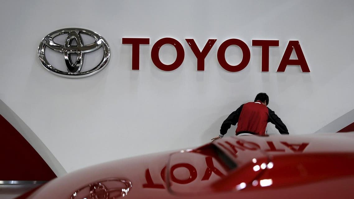 An employee works under a Toyota Motor Corp logo at the company's showroom in Tokyo, Japan February 5, 2016. Reuters