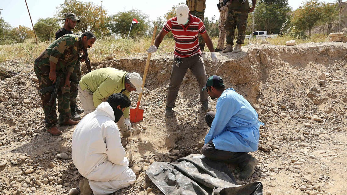An Iraqi forensic team works at the site of a mass grave, believed to contain the bodies of Iraqi soldiers killed by Islamic State group militants when they overran Camp Speicher military base last June, in Tikrit, Iraq, 80 miles (130 kilometers) north of Baghdad, Thursday, April 9, 2015. (AP Photo/Karim Kadim)