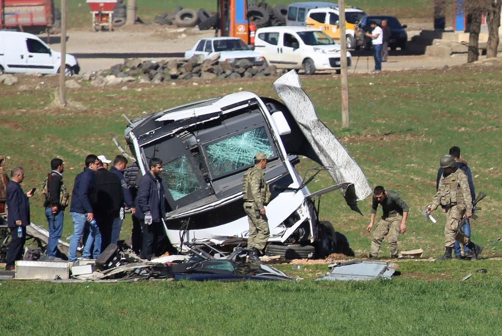 Members of Turkish forces gather around a bus that was destroyed in an explosion on the road linking the cities of Diyarbakir and Bingol, in southeastern Turkey, Thursday, Feb. 18, 2016. Six soldiers were killed after PKK rebels detonated a bomb on the road as their vehicle was passing by, according to Turkey's state-run Anadolu Agency.The deaths come a day after a suicide bombing claimed the lives of at least 28 people and wounded dozens of others. (AP Photo/Mahmut Bozarslan)