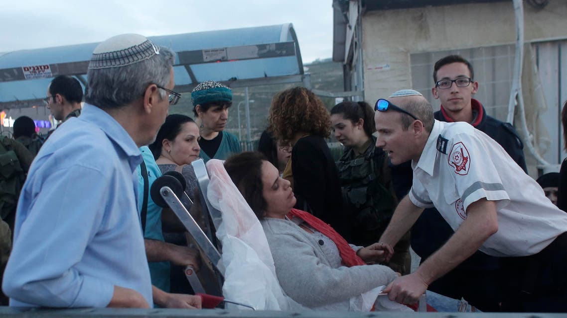 An Israeli woman (C) is treated for shock outside the Rami Levi supermarket in Shaar Binyamin, near Ramallah in the Israeli occupied West Bank, after two Palestinians carried out a stabbing attack on two Israeli men on February 18, 2016. AFP