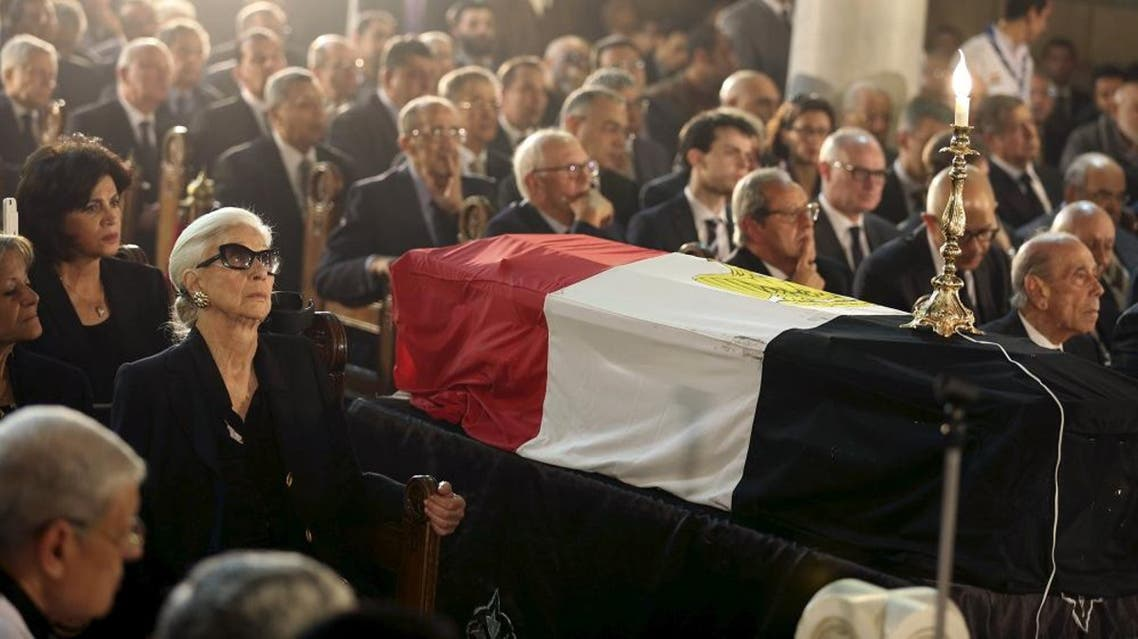 Leia Maria Boutros-Ghali (L), widow of Former U.N. Secretary-General Boutros Boutros-Ghali, sits next to his flag-draped coffin at the Saints Peter and Paul Coptic Orthodox church in Abassya district in Cairo, Egypt, Feburary 18, 2016. Former U.N. Secretary-General Boutros Boutros-Ghali, a blunt-spoken Egyptian who led the world body through global turmoil as it defined its peacekeeping role and lost his job over disputes with Washington, died on Tuesday. He was 93. REUTERS/Mohamed Abd El Ghany