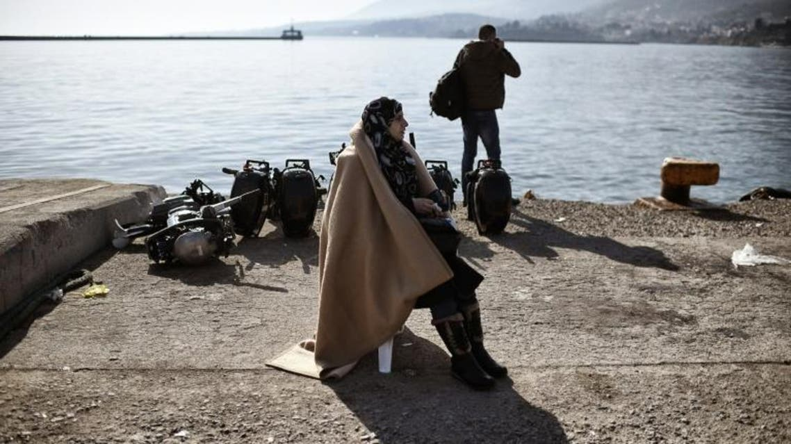 A migrant woman waits at the port of Mytilene, on the Greek island of Lesbos, after crossing the Aegean sea from Turkey. (AFP)