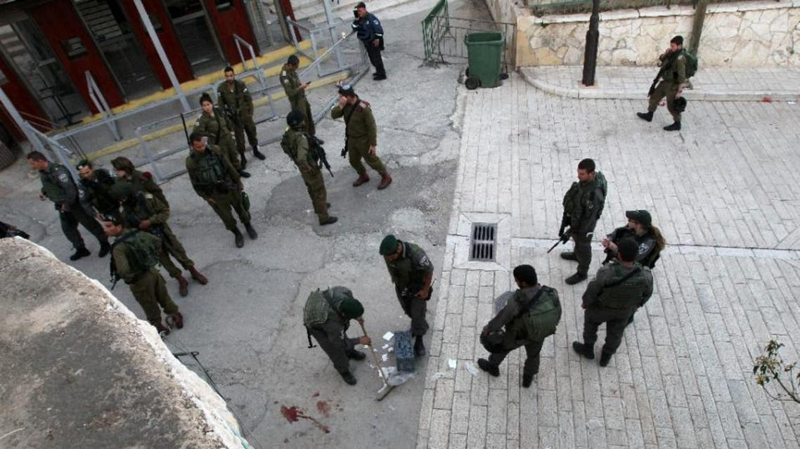 Israeli security forces clean the pavement at the site where a Palestinian was shot dead after stabbing a border policeman on April 25 2015 near the Tomb of Patriarchs in the West Bank city of Hebron. AFP, Hazem Bader (AFP)