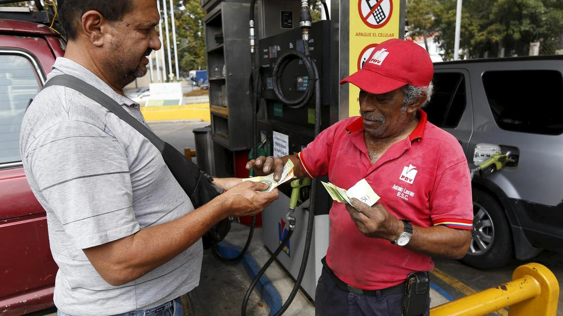 A man pays after filling up his car with fuel at a gas station which belongs to PDVSA in Caracas, Venezuela February 19, 2016. (Reuters)