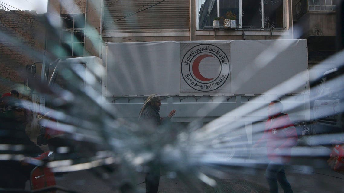 A Red Crescent aid convoy is pictured through a broken windshield in the rebel held besieged city of Douma, a suburb of Damascus February 13, 2016. Reuters