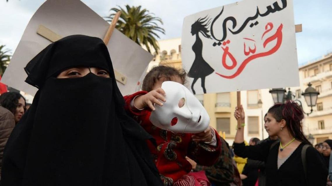 A Moroccan holding her child walks past supporters of the February 20 pro-reform movement to mark the fifth anniversary of the movement's creation, on February 20, 2016 in the capital Rabat (AFP)