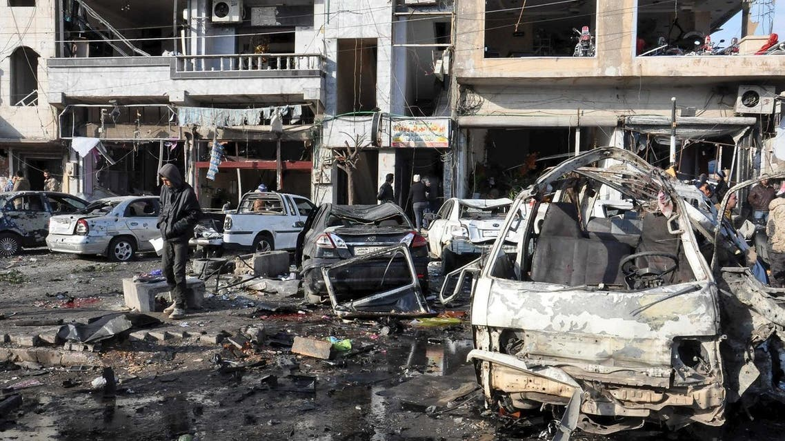 People inspect the site of a double bomb attack in the government-controlled city of Homs, Syria, in this handout picture provided by SANA on January 26, 2016. REUTERS
