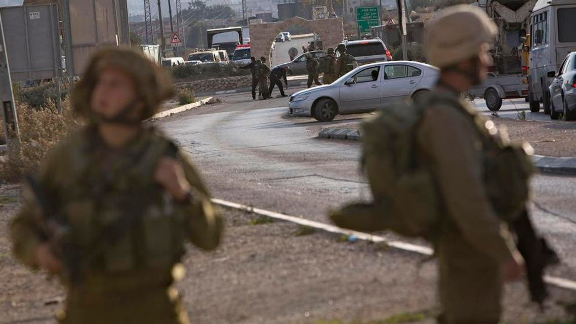 Israeli soldiers stand at the scene of a stabbing attack, at the Hawara checkpoint near of the West Bank city of Nablus, Monday, Nov. 23, 2015. The Israeli military said a Palestinian was shot dead as he tried to stab a soldier at the checkpoint. (AP Photo/Majdi Mohammed)