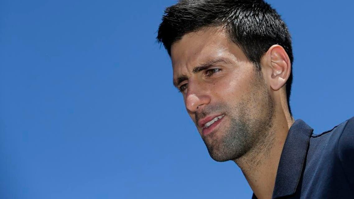 Serbia's Novak Djokovic talks to reporters following a photo shoot with his Australian Open trophy at Government House in Melbourne, Australia, Monday, Feb. 1, 2016. Djokovic defeated Britain's Andy Murray in the men's final at the Australian Open tennis championships on Sunday, Jan. 31.(AP Photo/Aaron Favila)
