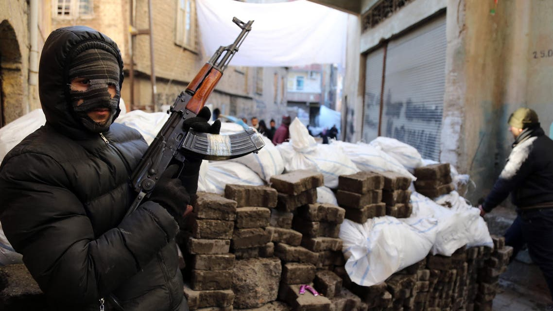 """A PKK militant stands at a barricade as some of thousands of people flee from the historic Sur district of the mainly-Kurdish city of Diyarbakir, Turkey, Wednesday, Jan. 27, 2016, after authorities, fighting Kurdish militants there, expanded a 24-hour curfew to include five more neighborhoods. The curfew in Sur, in place since December, was enlarged on Wednesday to enable the security forces to """"restore public order"""" in neighborhoods where militants linked to the Kurdistan Workers' Party, or PKK, had allegedly dug trenches, set up barricades and explosive devices. Turkey's military said three security force members were killed in an attack in Sur on Wednesday while the Dogan news agency reported heavy fighting in the neighborhood.(AP Photo/Murat Bay)"""