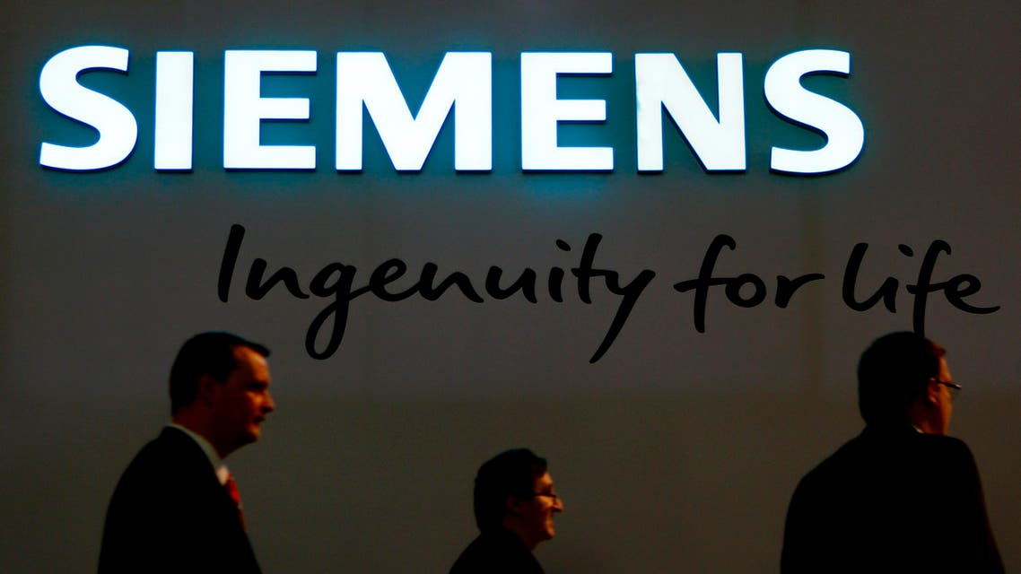 People walk past the new company logo of German industrial conglomerate Siemens in Munich, Germany, Tuesday, Jan. 26, 2016. (AP Photo/Matthias Schrader)