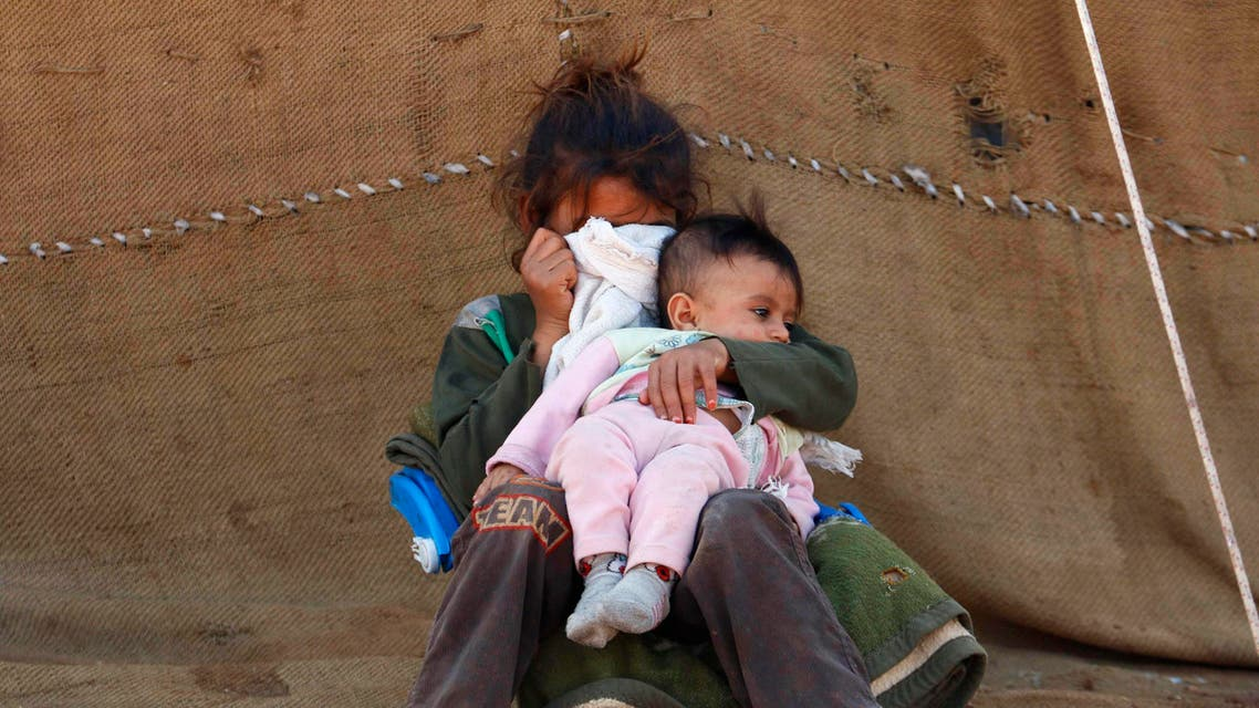 An internally displaced girl, who along with her family fled the violence in Aleppo's Handarat area, covers her face as she holds a child outside a tent in the northern countryside of Aleppo October 8, 2014. (Reuters)