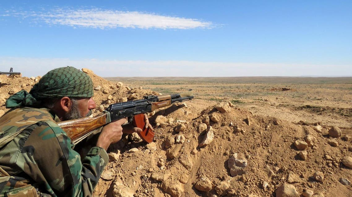 A Syrian army soldier takes aim from a position on the outskirts of Syria's Raqqa region. (AFP)