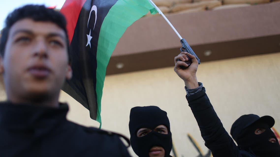 Libyan security forces stand in front of the security headquarters, one showing his weapon with a Libyan flag, in the western city of Sabratha, Libya, Saturday, Feb. 20, 2016. (File photo: AP)