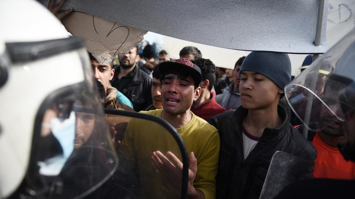 Greek policemen block Afghan refugees before the Greek-Macedonian borderline near the northern Greek village of Idomeni, Monday, Feb. 22, 2016. AP