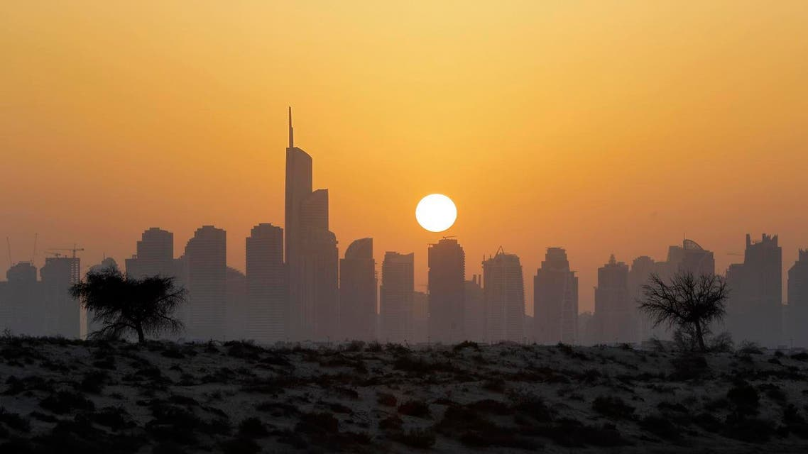 The sun sets behind the city skyline at the Marina district as the Almas tower is seen in Dubai, United Arab Emirates. (AP)