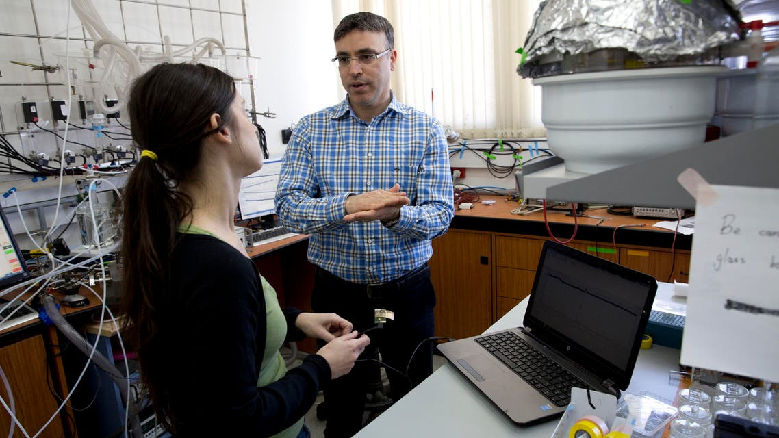 In this Sunday, Feb. 14, 2016 photo, professor Hossam Haick talks to a researcher in his lab at Technion University in Haifa, Israel.ap