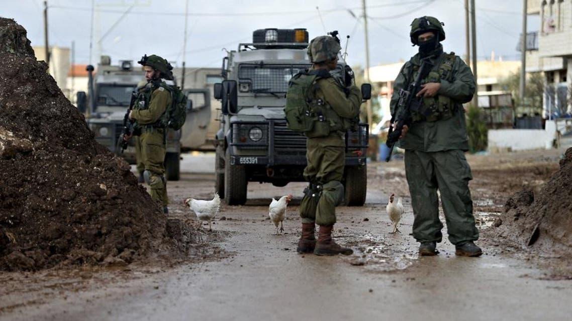Israeli soldiers standing guard in the West Bank town of Qabatya, near Jenin February 22, 2016