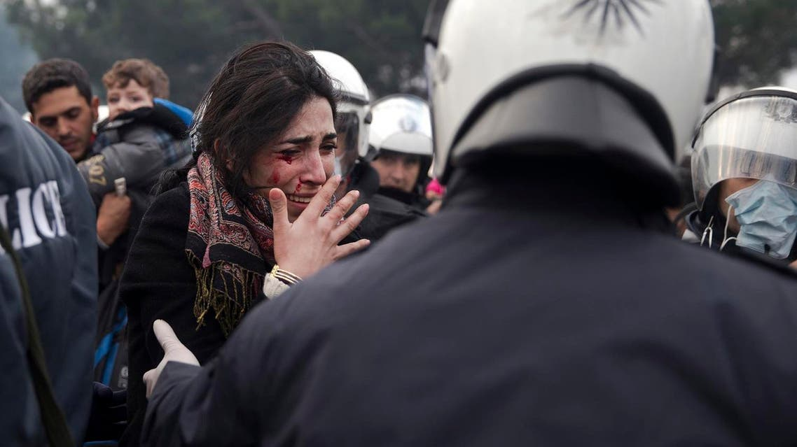 A bleeding woman reacts after a rock was thrown at her a little before crossing into Macedonia at the northern Greek border station of Idomeni, Friday, Dec. 4, 2015. (AP)