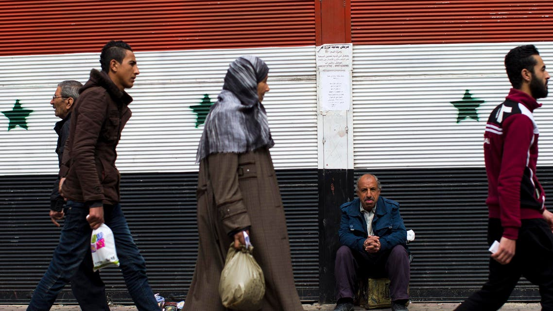 Syrians walk past a shop with a painting of the national flag in Damascus, Syria, Tuesday, Feb. 23, 2016. (AP)