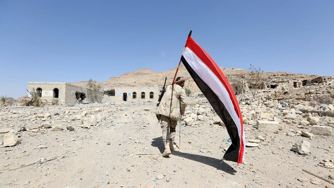 A pro-government army soldier carries Yemen's national flag as he walks at the strategic Fardhat Nahm military camp, around 60km  from Yemen's capital Sanaa. (Reuters)